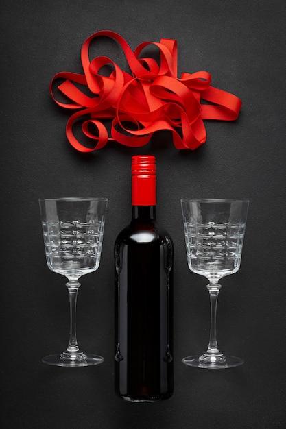 Bottiglia di vino rosso, bellissimi bicchieri per vino e un nastro rosso. Foto Premium