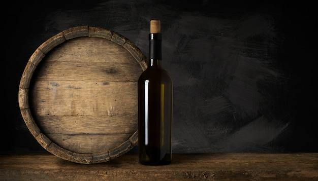 Bottiglia di vino rosso con un cavatappi. su uno sfondo di legno nero. Foto Premium