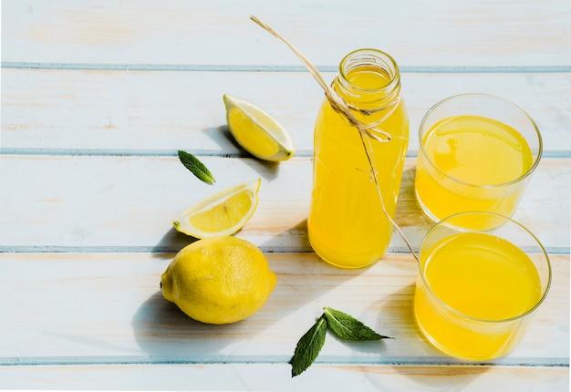 Bottiglia e bicchieri con cocktail di limone sul tavolo di legno squallido Foto Gratuite