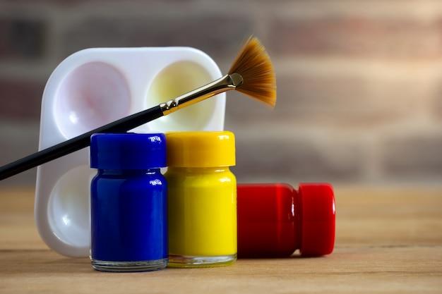 Bottiglia, pennello e tavolozza di colore del manifesto sulla tavola di legno Foto Premium