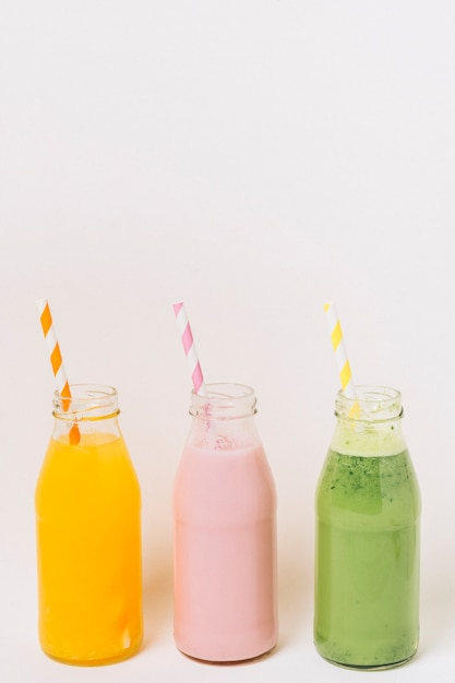 Bottiglie colorate con frullati di frutta Foto Gratuite