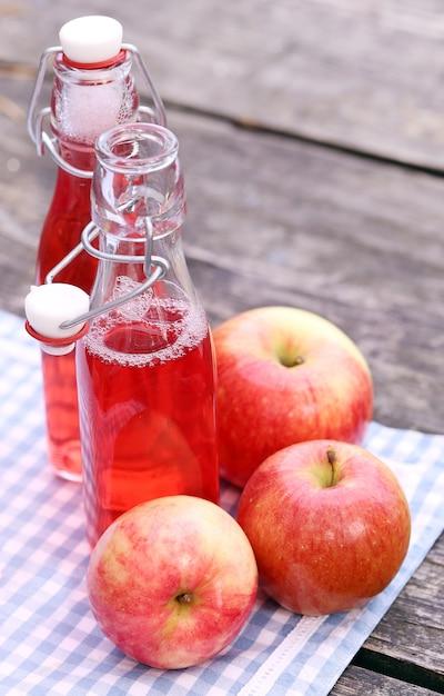 Bottiglie con bevande rosse e alcune mele Foto Gratuite