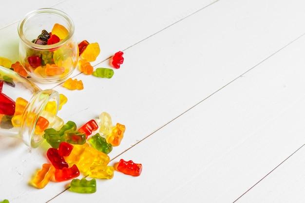 Bottiglie con caramelle dolci sul fondo della tavola Foto Premium