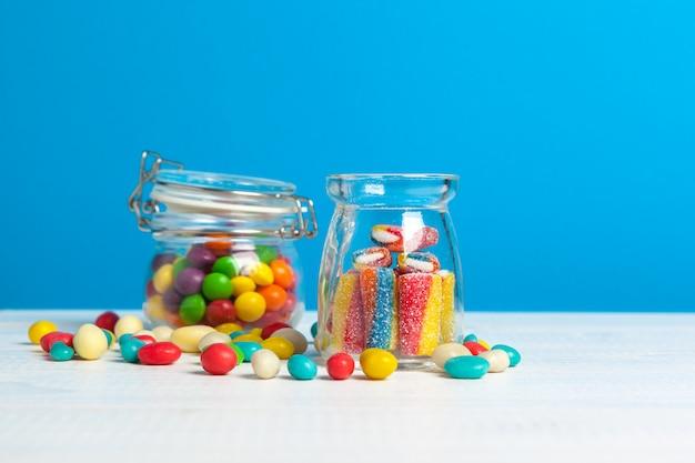 Bottiglie con caramelle dolci sul tavolo Foto Premium