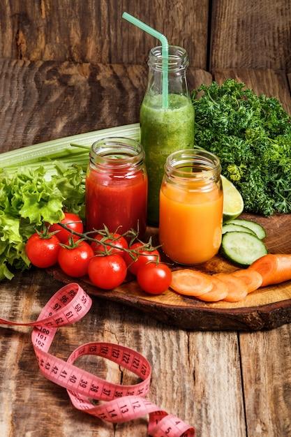 Bottiglie con succhi di verdura fresche sul tavolo di legno Foto Gratuite