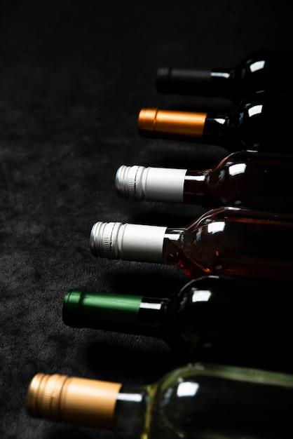 Bottiglie di alta vista di vino con sfondo nero Foto Gratuite