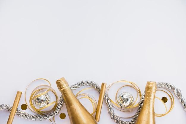 Bottiglie di bevanda vicino a tinsel e nastro Foto Gratuite