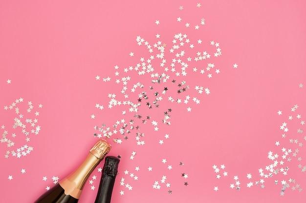 Bottiglie di champagne con stelle di coriandoli su sfondo rosa. copia spazio, vista dall'alto Foto Premium