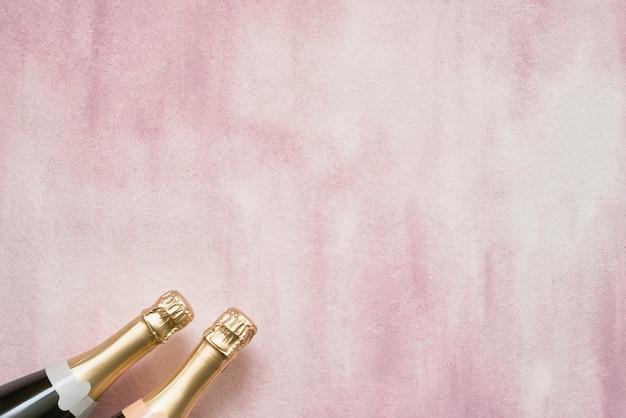 Bottiglie di champagne su sfondo rosa. Foto Premium