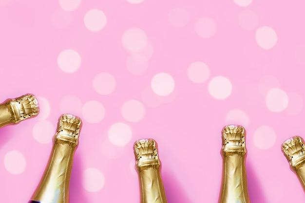 Bottiglie di champagne su uno sfondo rosa pastello con luci bokeh Foto Premium