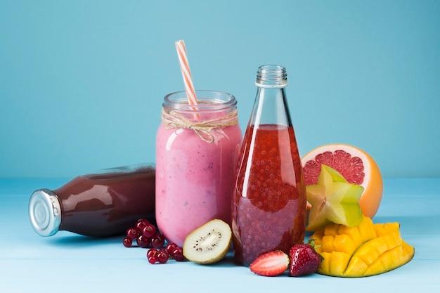 Bottiglie di frullato colorato e frutta Foto Gratuite