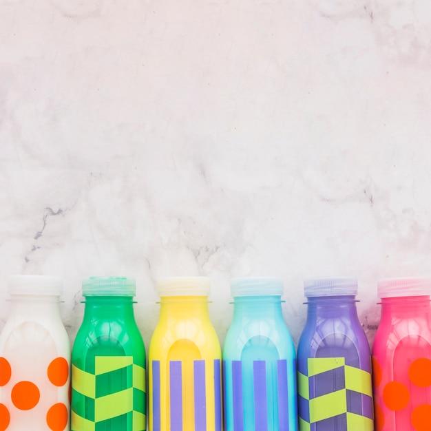 Bottiglie di latte colorate sul tavolo Foto Gratuite