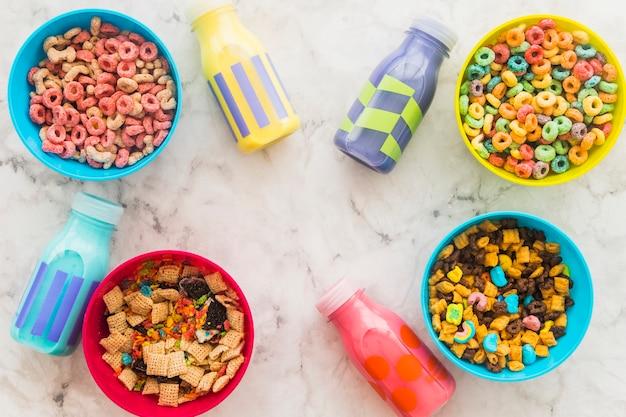 Bottiglie di latte con ciotole di cereali sul tavolo Foto Gratuite