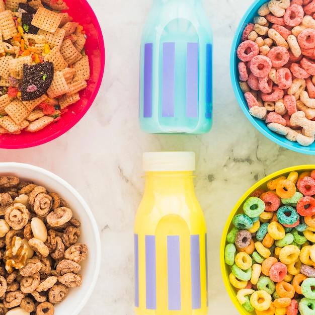 Bottiglie di latte con ciotole luminose di cereali sul tavolo Foto Gratuite