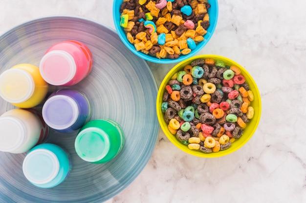 Bottiglie di latte sul piatto con ciotole di cereali Foto Gratuite
