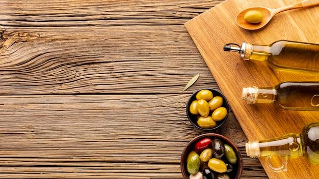 Bottiglie di olio di oliva ciotole e cucchiaio di legno con spazio di copia Foto Gratuite