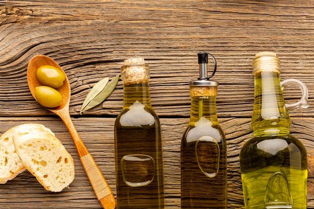 Bottiglie di olio piatto laici e cucchiaio di legno Foto Gratuite