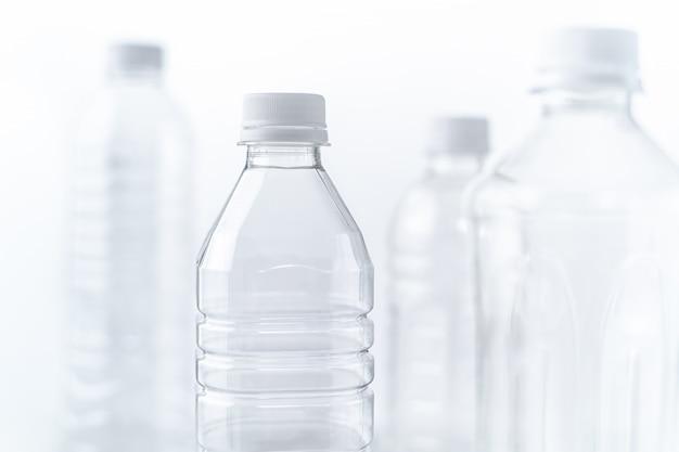 Bottiglie di plastica in varie forme e dimensioni sul tavolo bianco e lo sfondo Foto Premium