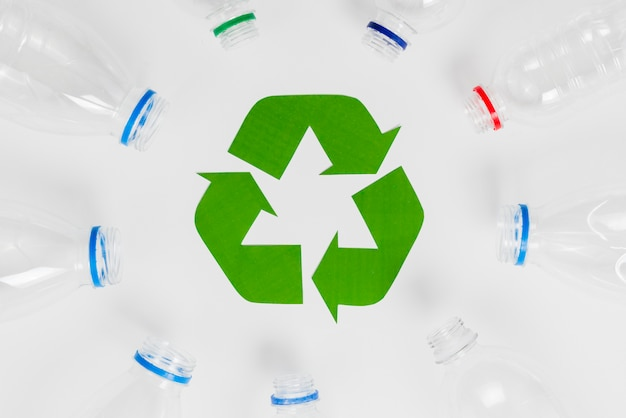 Bottiglie di plastica vuote intorno all'icona di riciclaggio Foto Gratuite