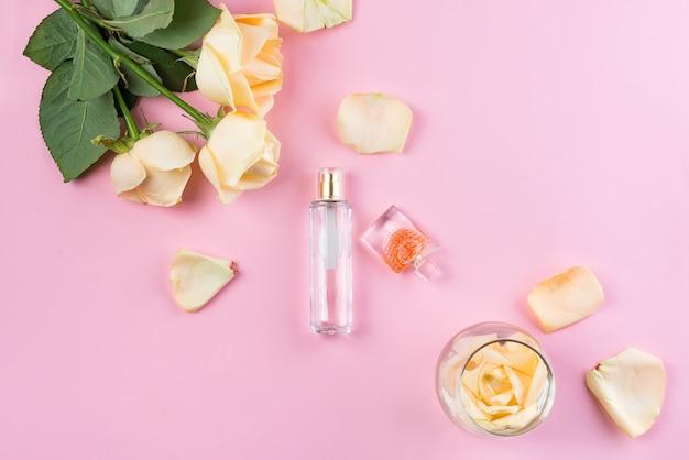 Bottiglie di profumo con fiori su sfondo rosa. profumeria, cosmetici, collezione di profumi. distesi Foto Premium