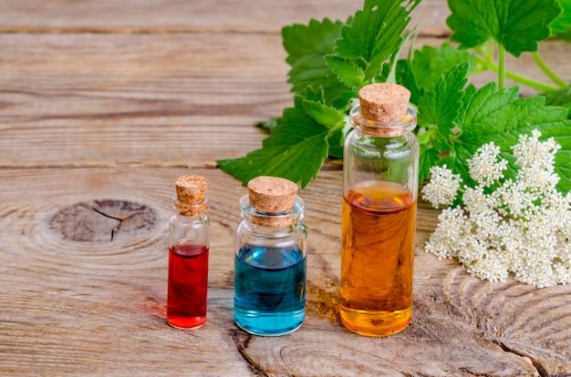 Bottiglie di vetro di aroma di olio essenziale su legno, immagine per la medicina terapia alternativa Foto Premium