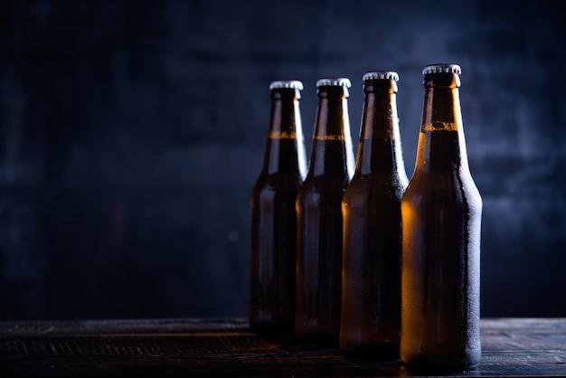 Bottiglie di vetro di birra con vetro e ghiaccio su sfondo scuro Foto Gratuite