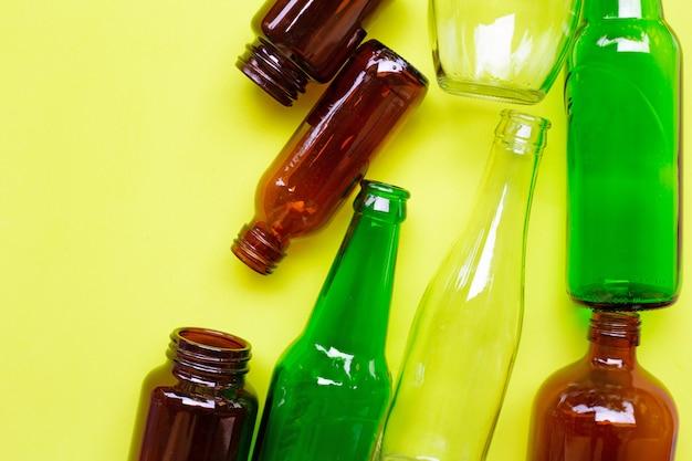Bottiglie di vetro su sfondo giallo verde. Foto Premium