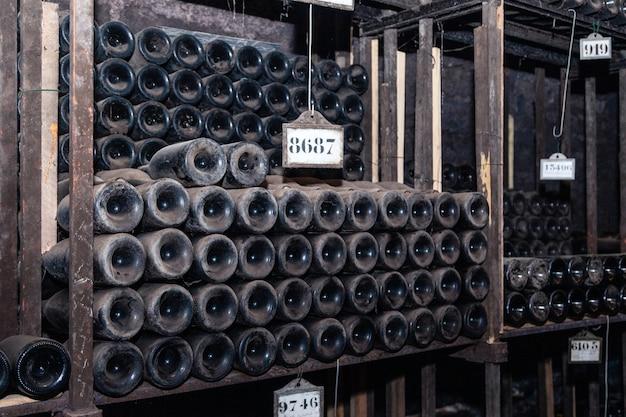 Bottiglie di vino antiche che invecchiano nella cantina sotterranea nelle file Foto Premium