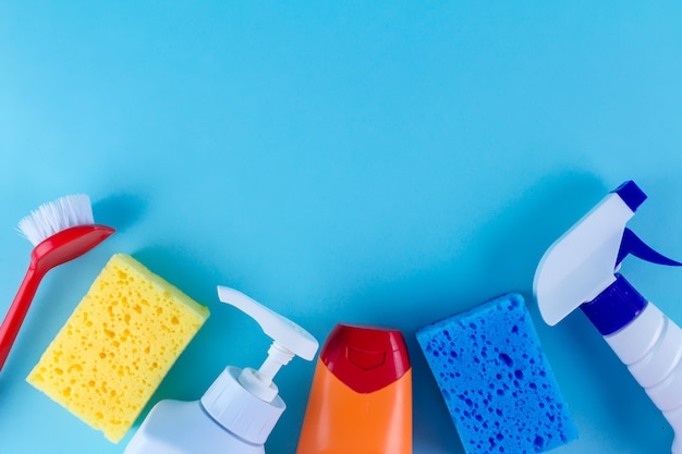 Bottiglie, spray per pulire la casa, spugne colorate per lavare i piatti e un pennello Foto Premium