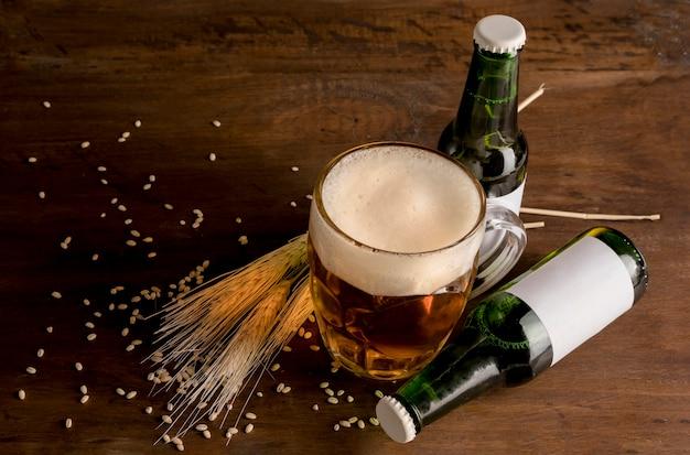 Bottiglie verdi di birra con bicchiere di birra sulla tavola di legno Foto Gratuite