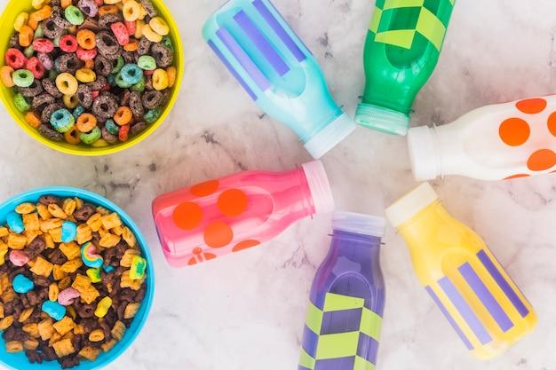 Bottigliette per il latte con ciotole di cereali sul tavolo Foto Gratuite