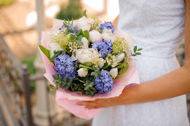 Bouquet da sposa con pioni nelle mani della sposa Foto Premium
