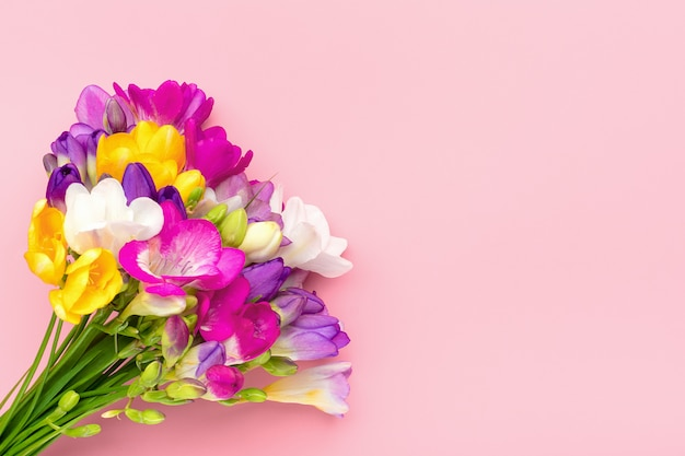 Bouquet di fiori di fresia rametto isolato su sfondo rosa biglietto di auguri floreale vista dall'alto piatto lay Foto Premium