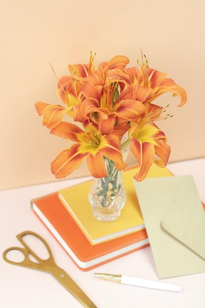 Bouquet di gigli arancioni con forbici d'oro e busta artigianale Foto Premium