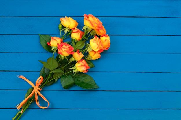 Bouquet di rose arancioni su legno blu Foto Premium