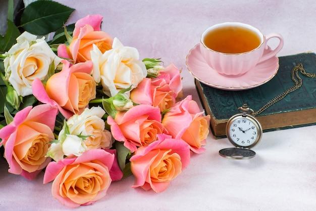 Bouquet di rose rosa e crema, una tazza di tè, un libro e un orologio da tasca Foto Premium