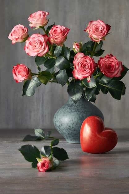 Bouquet di rose rosa e un cuore di pietra rossa sul buio Foto Premium
