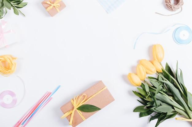 Bouquet di tulipani gialli, scatole con regali, nastri e corda su un tavolo bianco, vista dall'alto Foto Premium