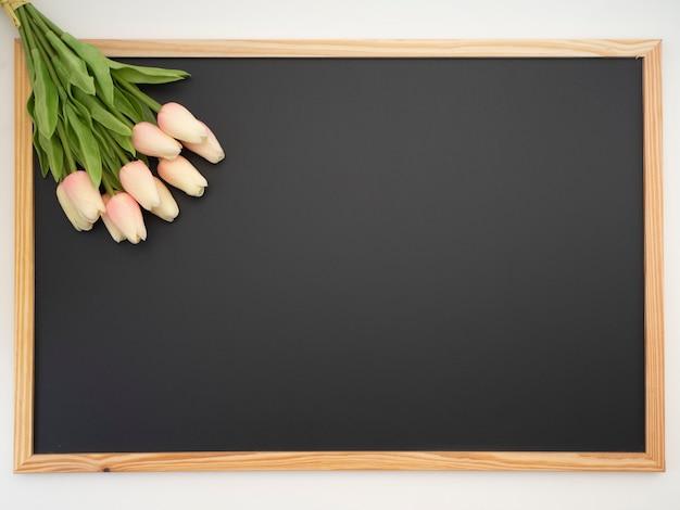 Bouquet di tulipani posto sulla cornice della lavagna Foto Premium