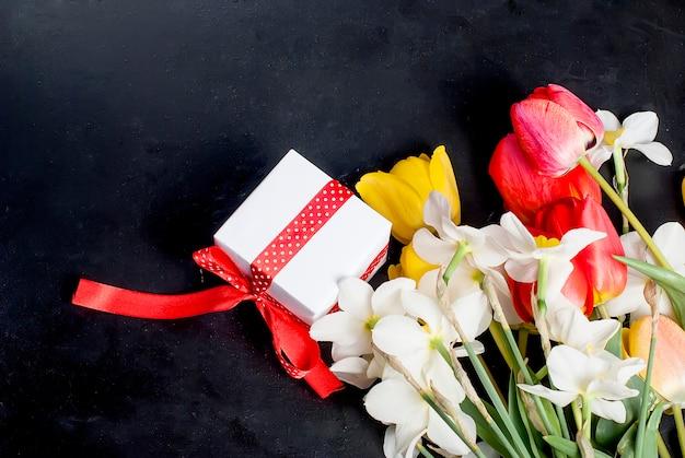 Bouquet di tulipani rossi, daffodils e regalo sullo sfondo nero Foto Premium