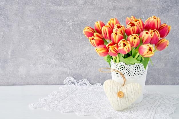 Bouquet di tulipani rossi in vaso decorato con cuore. san valentino, festa della mamma, concetto di compleanno. Foto Premium