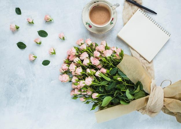 Bouquet fresco di rose rosa con una tazza di caffè; blocco note a spirale e penna su sfondo con texture Foto Gratuite