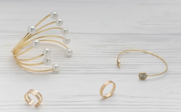 Braccialetti ed anelli della perla e del diamante dorati su superficie di legno bianca Foto Premium