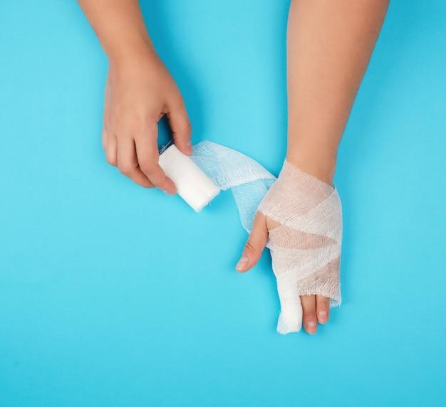 Braccio avvolto in una benda bianca sterile su sfondo blu Foto Premium