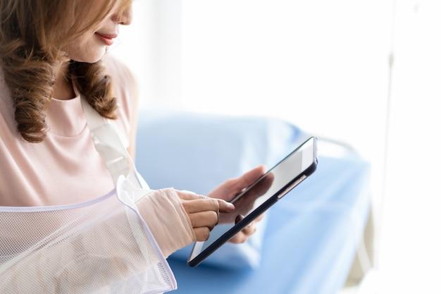 Braccio rotto donna asiatica che si siede sul letto in ospedale facendo uso di una compressa. concetto di assistenza sanitaria nello stile di vita moderno. Foto Premium