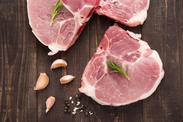 Braciola di maiale cruda di vista superiore con aglio e pepe su fondo di legno Foto Premium