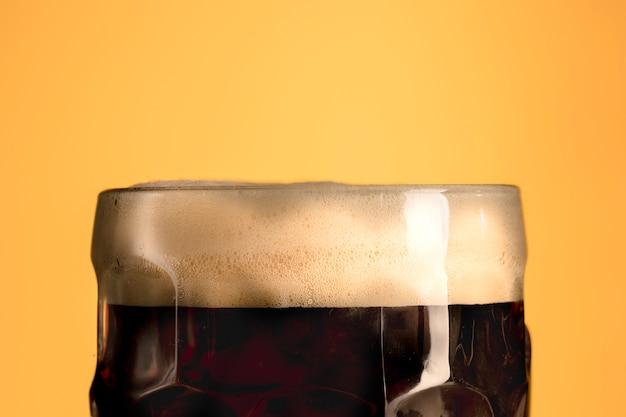 Brocca di birra fresca con schiuma su sfondo arancione Foto Gratuite