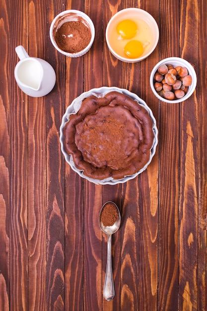 Brocca di latte; caffè in polvere di cioccolato; tuorlo d'uovo e nocciola per fare la torta fresca sulla superficie di legno Foto Gratuite