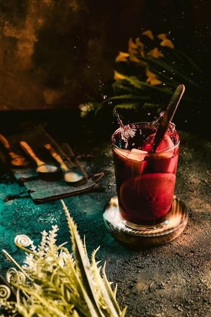 Brocca di sangria fredda con frutta su una superficie scura Foto Premium