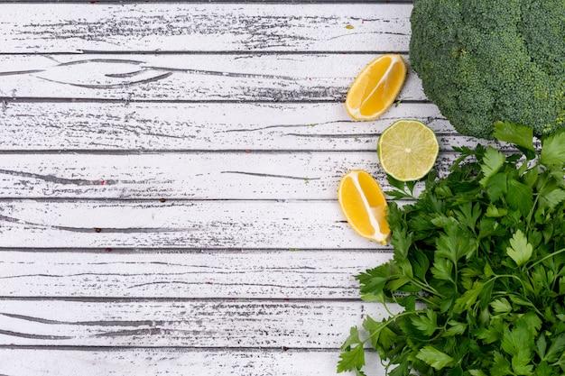 Broccoli limone e prezzemolo gialli con lo spazio della copia su superficie di legno Foto Gratuite